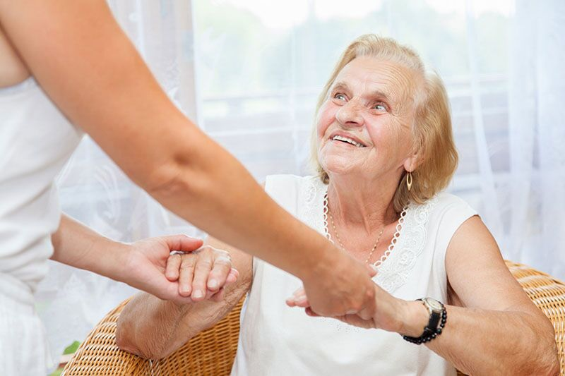 caregiver helping an elderly woman up, attract and keep talented caregivers on your staff