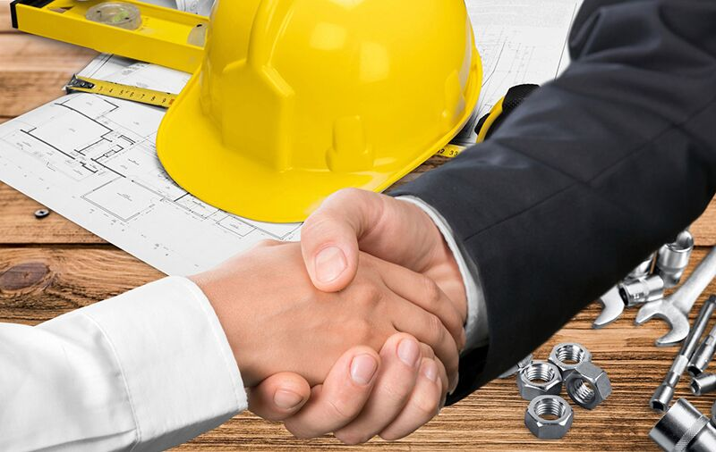 men shaking hands over blueprints, risk management strategies you should employ when it comes to working with independent contractors