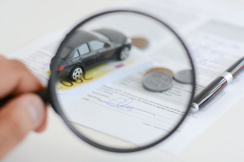 inspecting car insurance form with magnifying glass, Michigan auto insurance reform