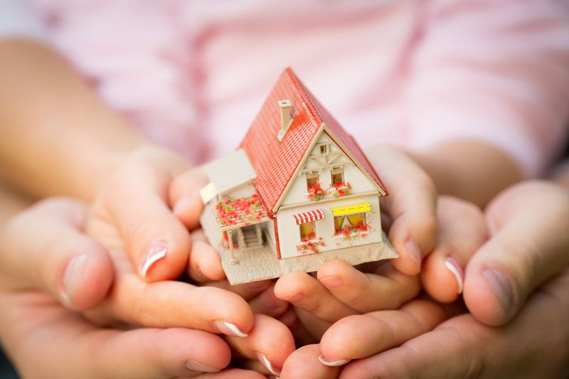 mother and daughter cradling toy home in hands, what to know about home insurance