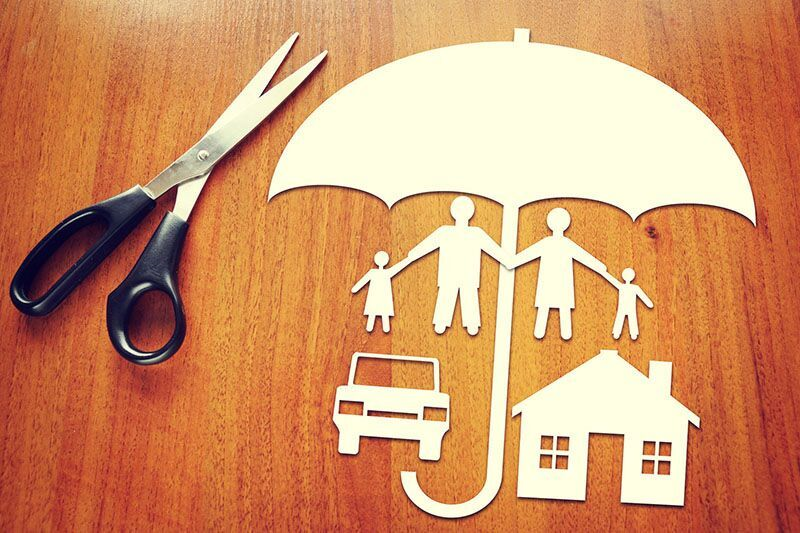 paper umbrella cutout shielding cutouts of a home, car, and family