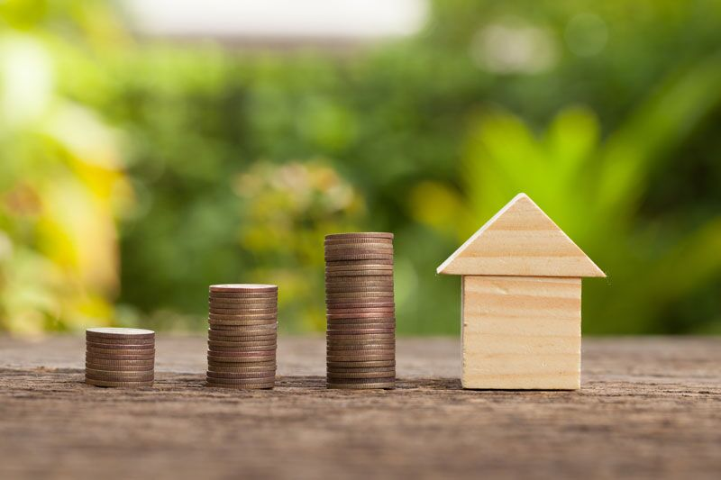 increasingly tall stacks of coincs next to a small wood house, factors that make your home insurance more expensive